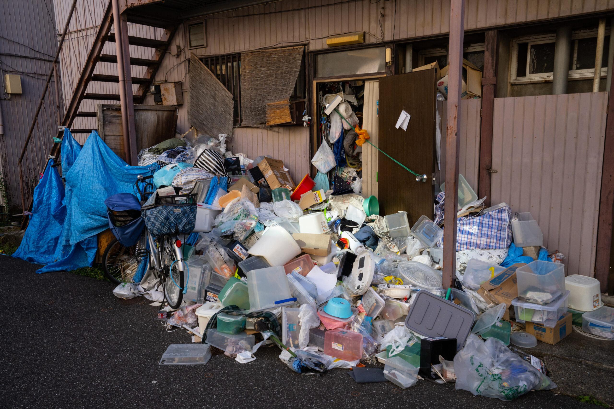 ゴミの山、ゴミ屋敷、積み上がったゴミに囲まれたアパート